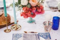 08 a bright Mediterranean wedding tablescape done with printed blue napkins and candles holders, light blue candles and azulejo tiles
