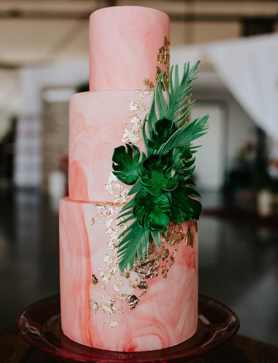 a marbleized coral wedding cake decorated with gold leaf and sugar tropical leaves is a chic idea for a tropical wedding
