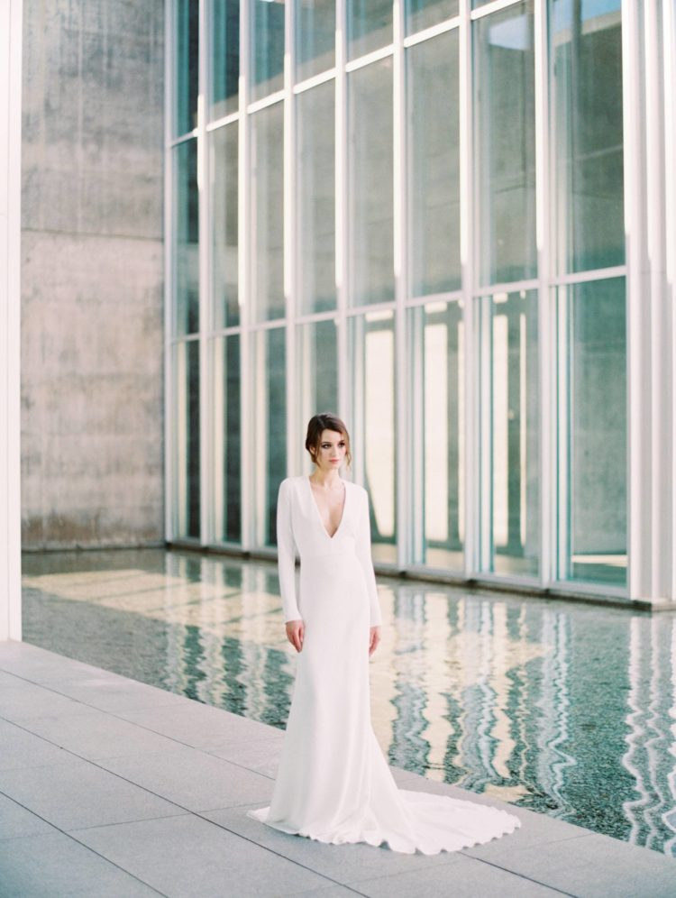 a minimalist wedding gown with a plunging neckline, long sleeves, a train for a Nordic bride