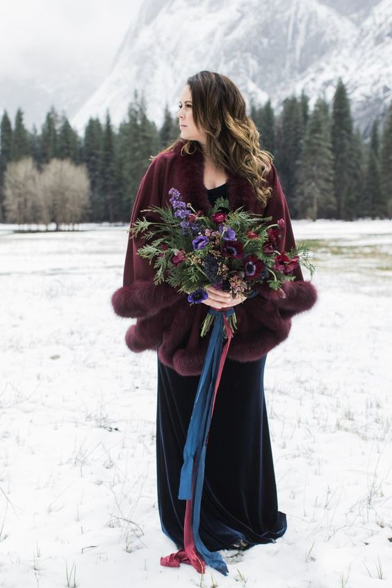 a statement plum-colored capelet with fur over a navy wedding dress is a gorgeous and bold idea