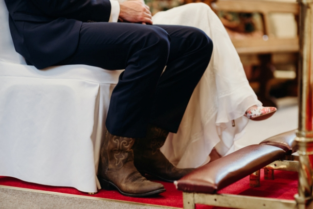 The groom was wearing a navy three piece suit, a white bow tie and brown cowboy boots