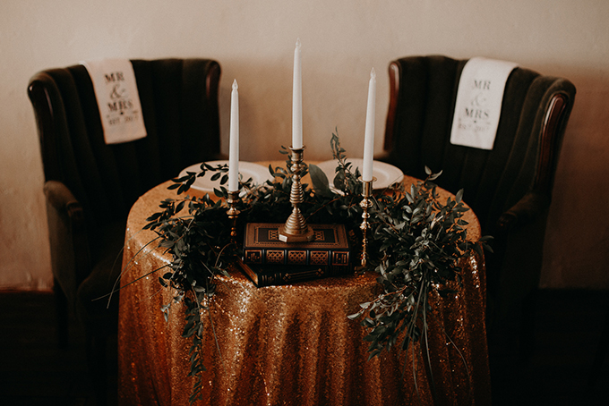 The sweetheart table was done with a gold sequin tablecloth, greenery and tall candles