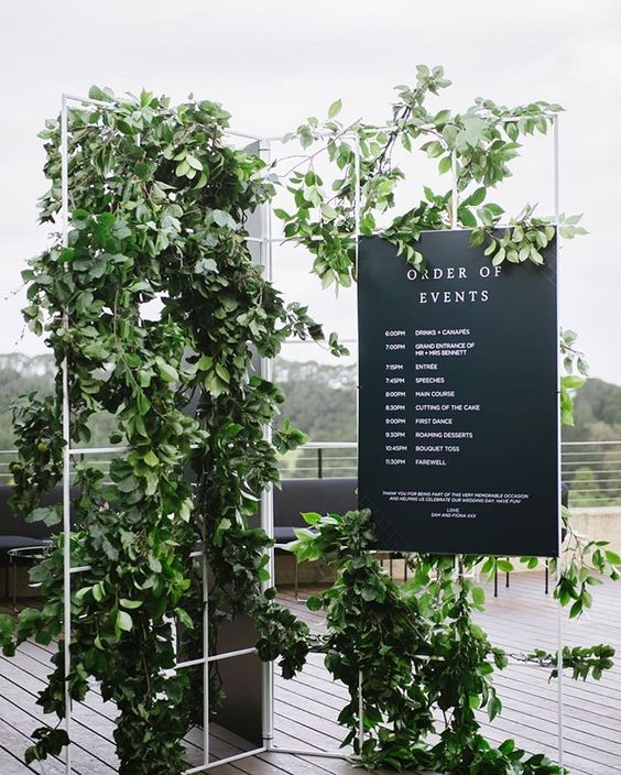 a beautiful wedding decoration of a grid, much fresh greenery and a black and white program for a modern Nordic wedding