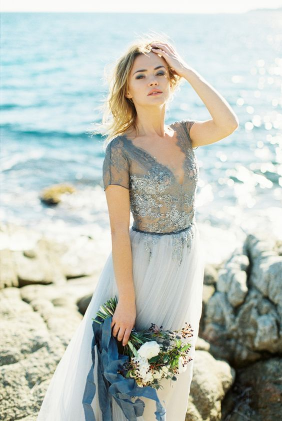 a blue wedding gown with a lace embellished bodice with short sleeves and a deep V necckline and a flowy skirt