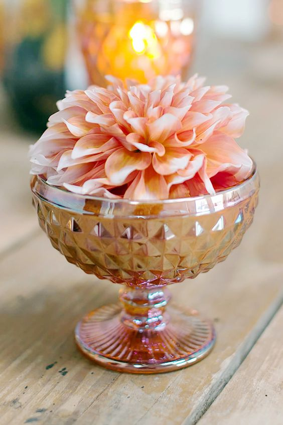 a copper bowl with a single large peachy bloom is a cool centerpiece idea for your reception table