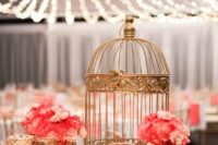 09 a gold sequin tablecloth, gold candle holders and a birdcage plus coral blooms for a glam wedding