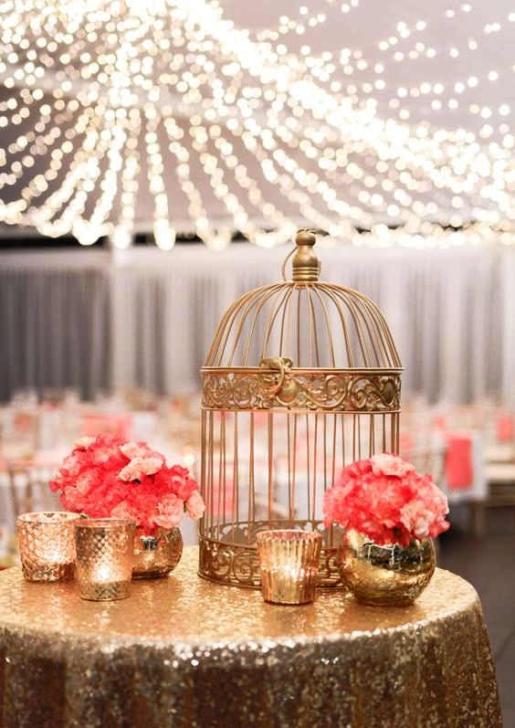a gold sequin tablecloth, gold candle holders and a birdcage plus coral blooms for a glam wedding
