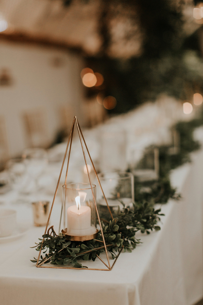 The tables were lined up with fresh greenery and candles in geometric candle holders