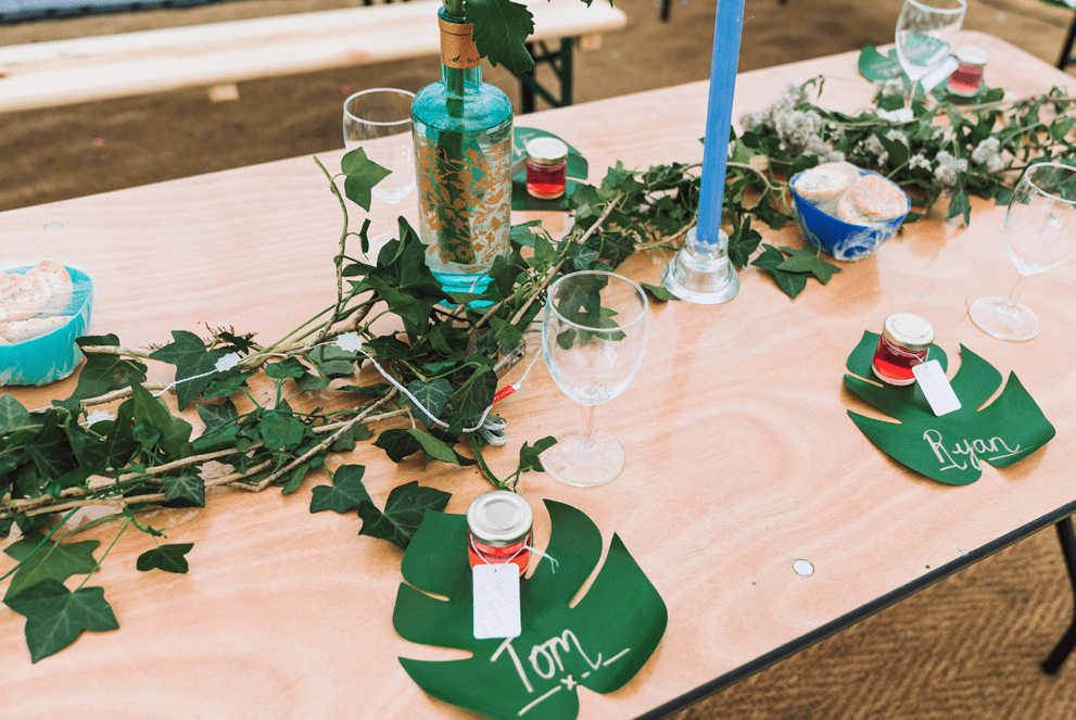 The wedding tables were decorated with greenery, with paper tropical leaves and homemade jam favors