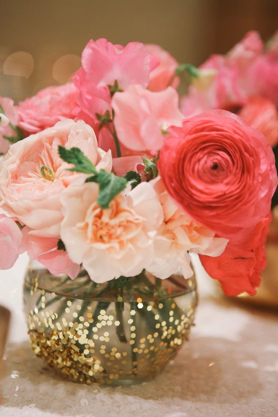 a colorful wedding centerpiece of a vase with gold sequins and blush and coral blooms is a great summer idea