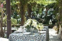 10 a cozy small wedding reception in a patio decorated with greenery and bright blooms, a bright printed tablecloth