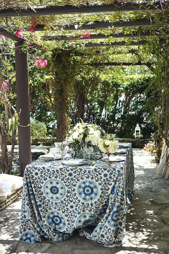 a cozy small wedding reception in a patio decorated with greenery and bright blooms, a bright printed tablecloth