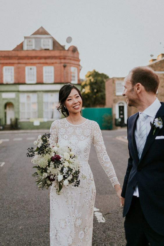 a lace embroidered wedding gown with an illusion neckline and long sleeves