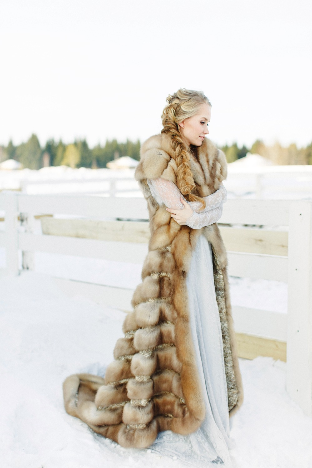a luxurious long fur coat without sleeves but with a train is a statement piece in this bridal outfit