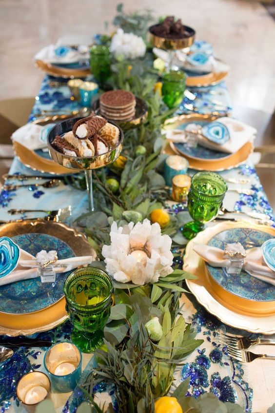 a Mediterranean wedding table setting done with blues, agate slices, beachy candle holders and a lush greenery and citrus table runner