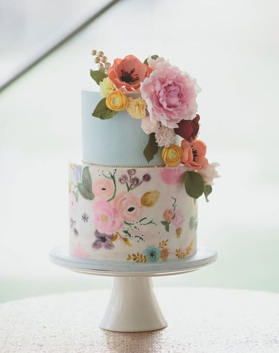 a colorful handpainted wedding cake with a light blue tier, a bright floral tier in various shades and sugar flower decor