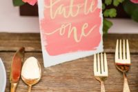 11 a watercolor coral and gold table number plus gold cutlery and coral blooms for a bright wedding tablescape
