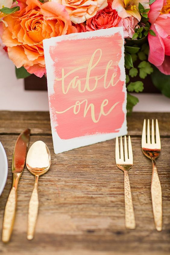 a watercolor coral and gold table number plus gold cutlery and coral blooms for a bright wedding tablescape