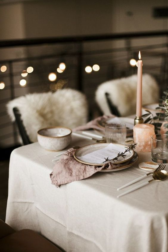 a wedding tablescape done in soft neutral and blush tones, with vintage ceramics and candles is a very hygge idea