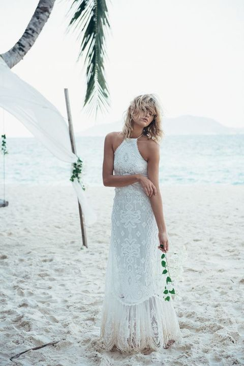 a boho beach lace wedding gown with a halter neckline is a trendy and chic idea for a boho bride