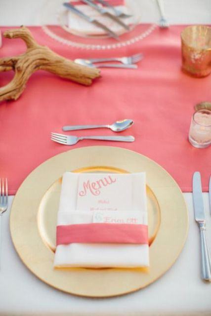 a bright tropical wedding table setting with a coral runner and napkin plis a gold charger and candle holders