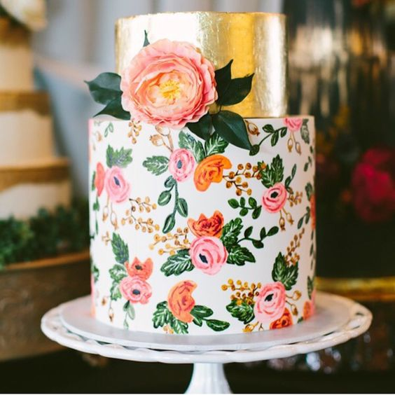a bright wedding cake with a gold foil tier and a colorful floral one in pink and orange with a real bloom on top