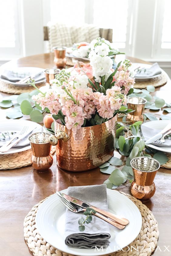 a cozy tablescape with copper hammered cups, a vase and peachy pink blooms plus wicker chargers