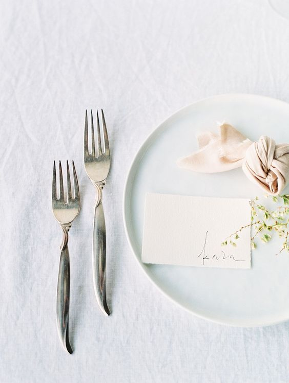 a minimalist Nordic place setting with a white charger, a blush napkin and some fresh greenery for spring