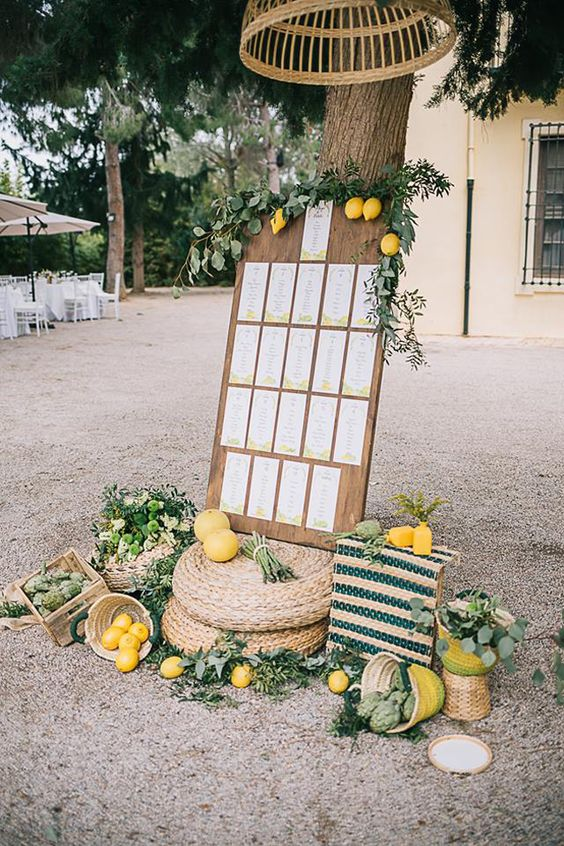 a stylish seating chart decorated with lemons, greenery, artichokes, striped textiles to feel Mediterranean