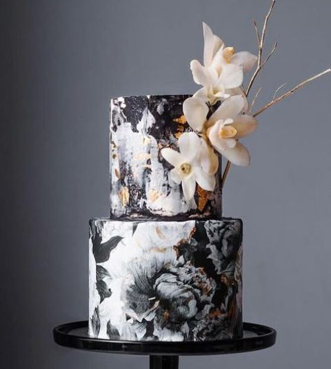 a black and white floral wedding cake with gold leaf decor and sugar blooms and gilded twigs for decor