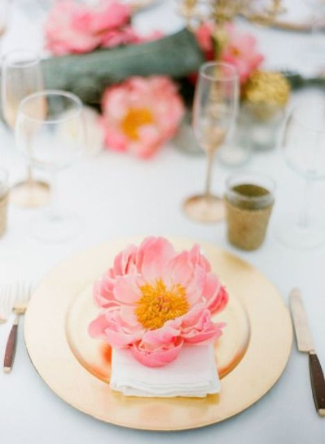 a chic and colorful table setting with a gold charger and a bold coral bloom is a great and bright idea