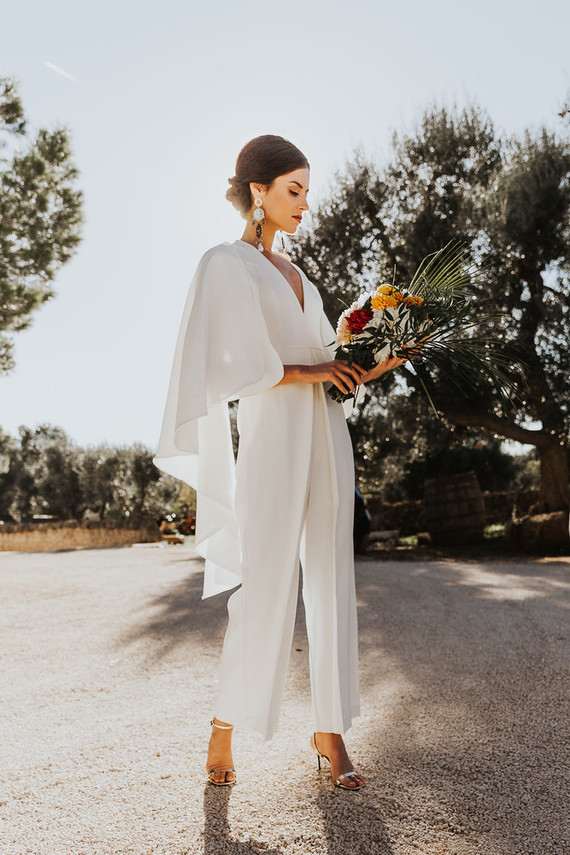 a fantastic minimalist white jumpsuit with a deep V-neckline, cape sleeves and statement earrings