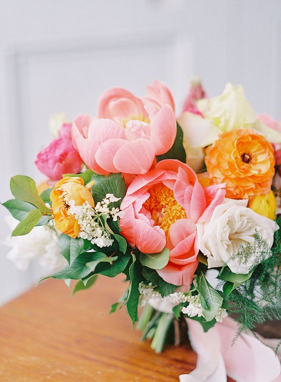 a lush and bright wedding bouquet with white, yellow and coral blooms will accent your bridal look