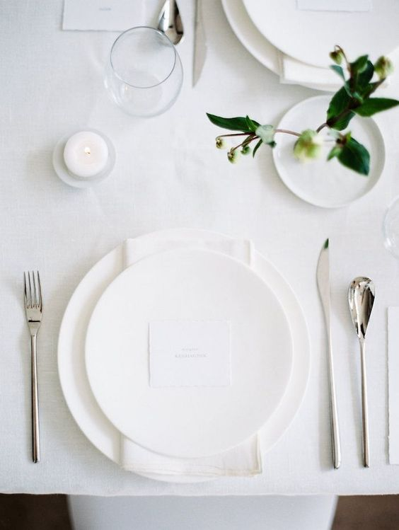 a minimalist Nordic tablescape in white, with plain porcelain, modenr cutlery and touches of greenery