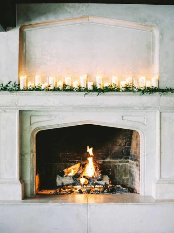 a fireplace with a fire and candles lining it up will add a right amount of light, too