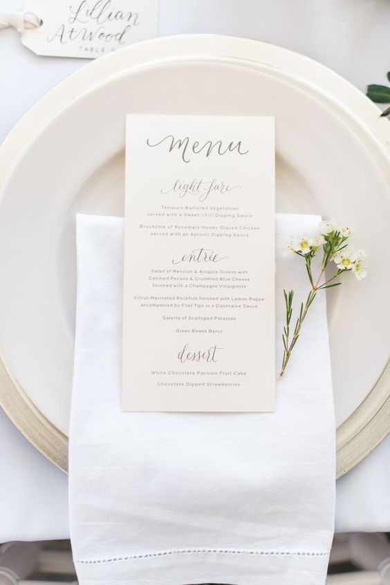 a minimalist spring inspired place setting with matte plates, a white napkin and a neutral card plus blooms