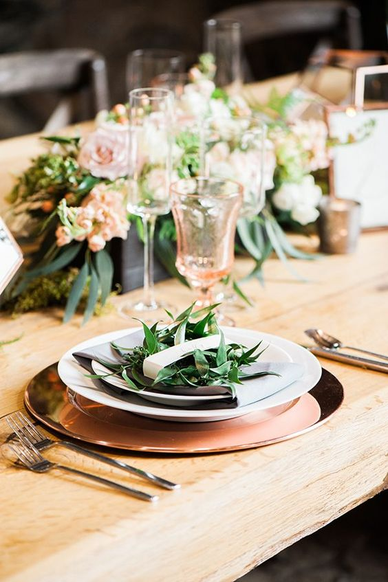 a polished copper charger, peachy glassware and peachy blooms in a lush wedding centerpiece