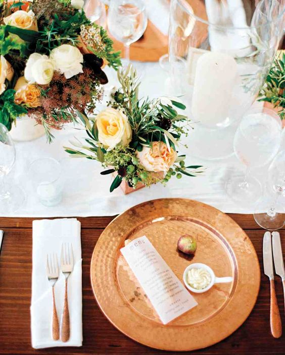 a stylish tablescape with a hammered copper charger, peachy blooms in the centerpiece refreshed with whites