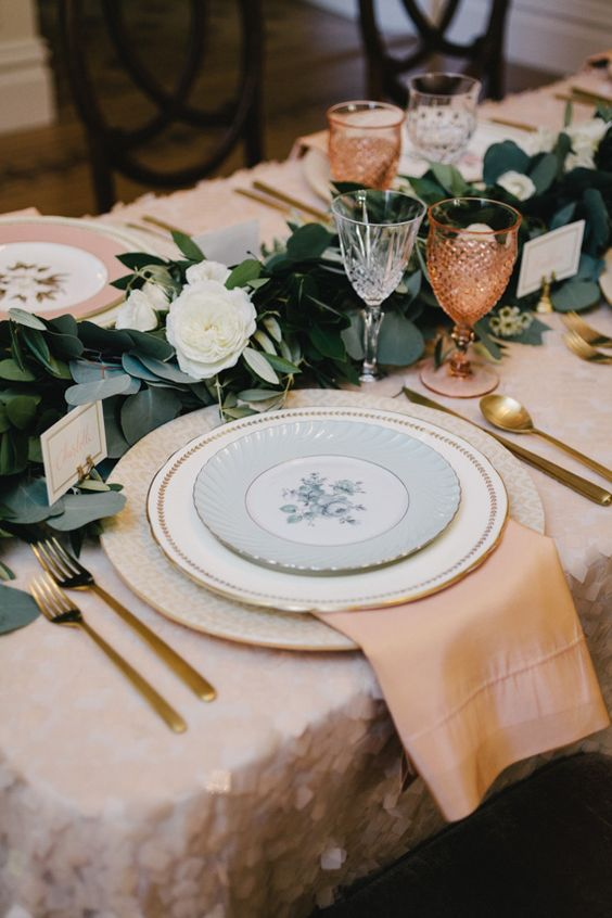 peachy napkins, copper glasses and a lush greenery and white bloom table runner plus gold cutlery