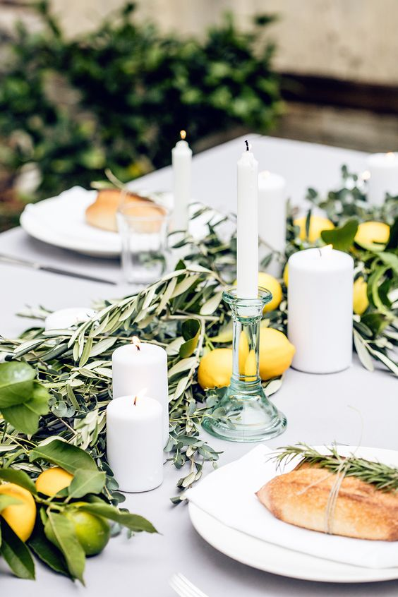 simple table styling with olive branches, lemons and limes plus white candles work well with a white tablecloth for a relaxed feel