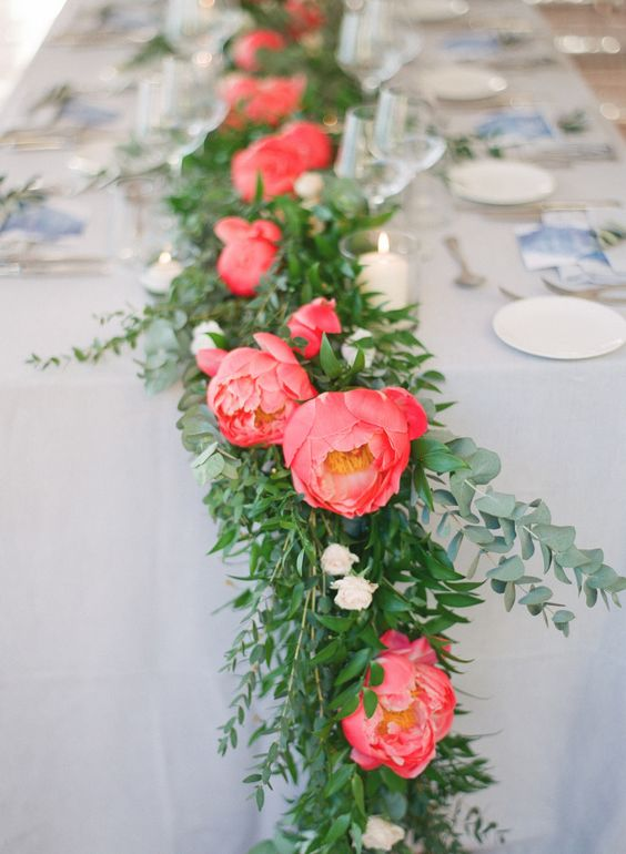 a bold wedding table runner with bold greenery and coral and blush blooms is a super catchy and fun idea
