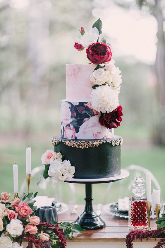 a bright and glam wedding cake with a watercolor pink tier, a black tier with gold decor and a handpainted floral tier plus fresh blooms