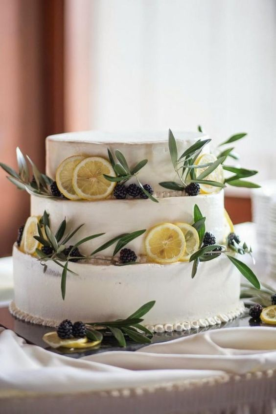 a buttercream wedding cake with citrus slices, blackberries and greenery is a cool idea for a Mediterranean wedding