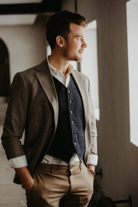 a relaxed layered groom's look with pants, a blazer, a navy waistcoat and a white shirt