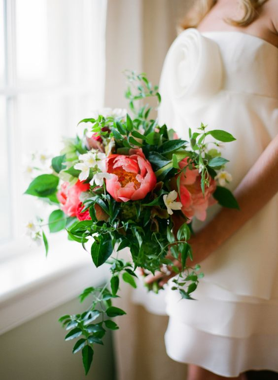 a bright wedding bouquet of fresh greenery and bold coral blooms plus cascading textures