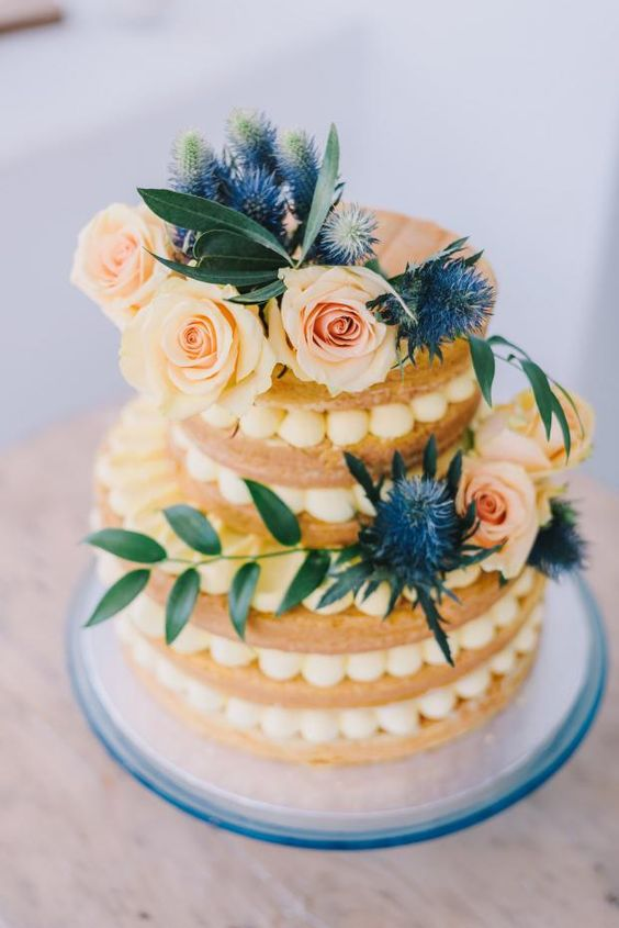 a delicious naked wedding cake topped with fresh blooms, thistles and greenery looks very Mediterranean-like