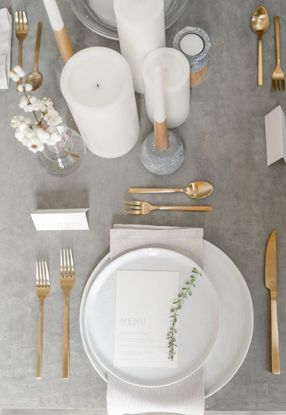 a minimalist wedding table setting with a grey tablecloth, gold cutlery and white candles looks ethereal