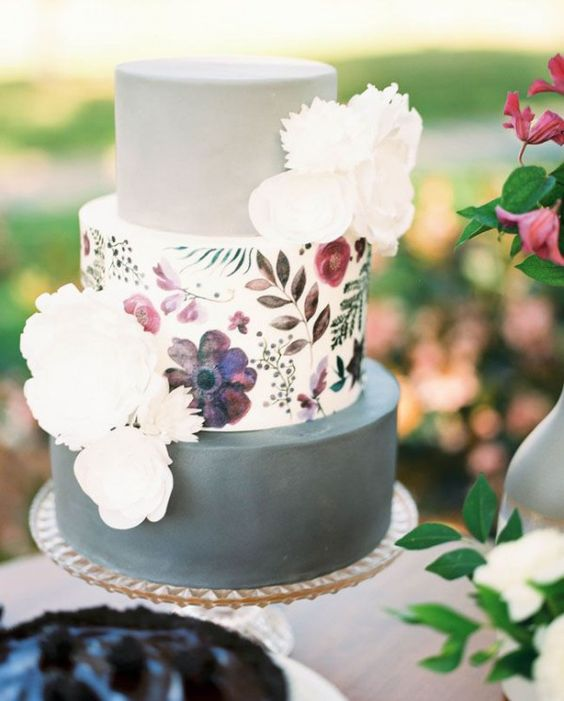 a modern wedding cake with two grey tiers and a floral painted tier in the center plus white sugar blooms