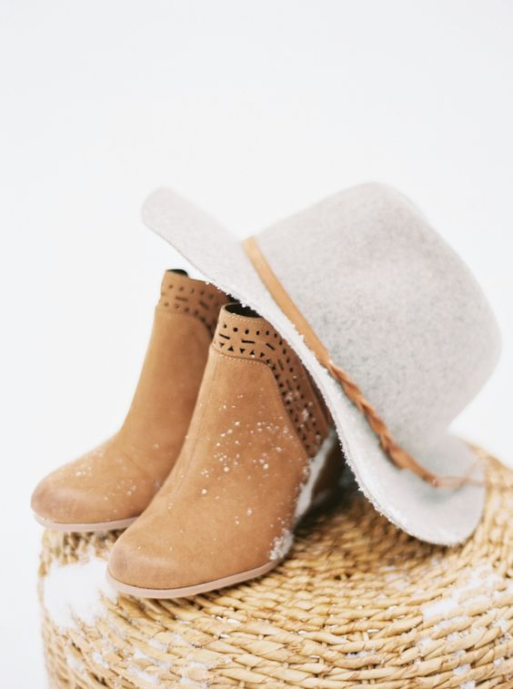 amber laser cut wedding boots and a hat with a matching ribbon for a boho winter bride