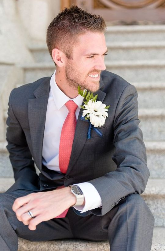 a cool groom's outfit with a grey suit, a white shirt and a coral tie plus a white bloom boutonniere for a summer wedding